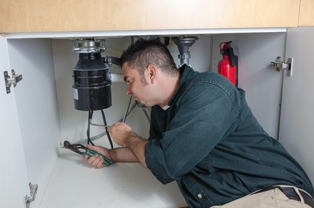 man on ground under sink holding blue handled wrench installing garbage disposal