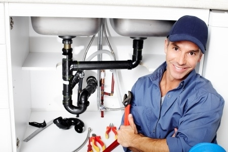 man sitting on floor in front of open cabinet showing drain for kitchen sink holding an orange wrench