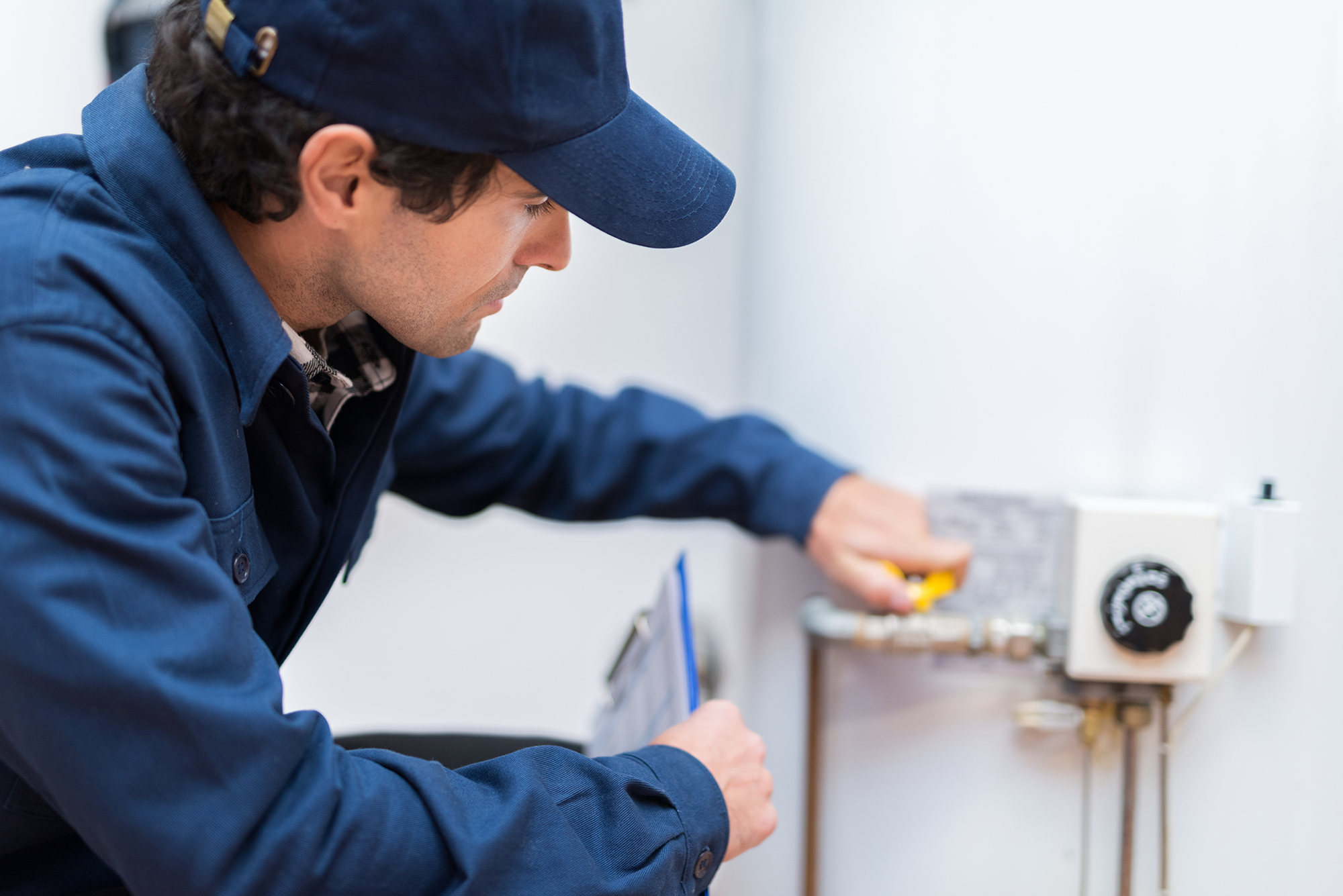 plumber in blue uniform with hat turning water valve
